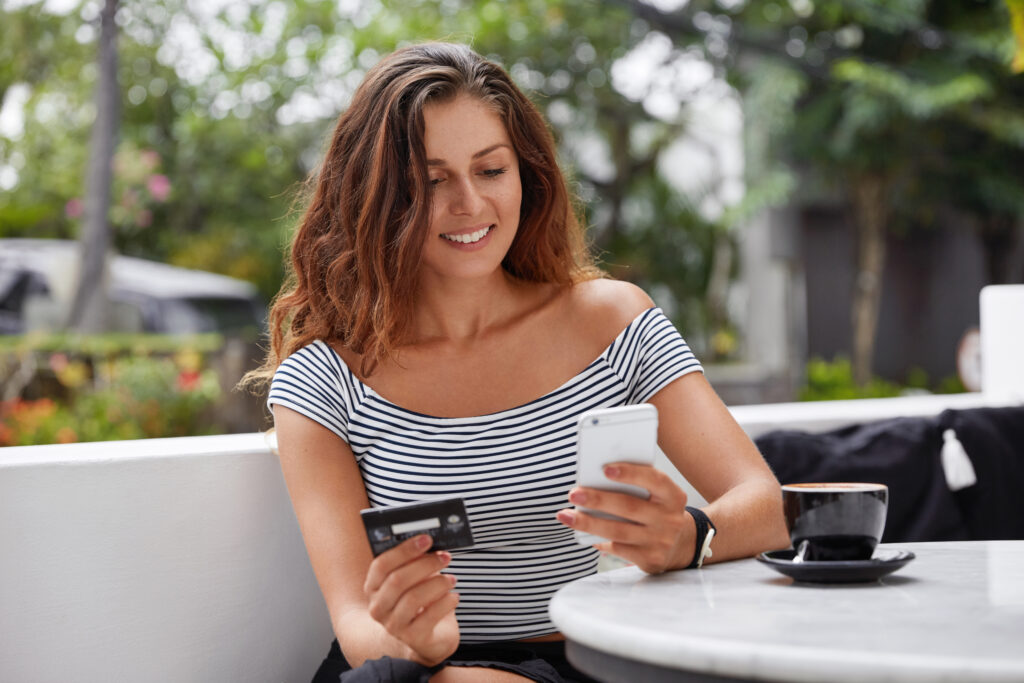 Good looking brunette female in fashionable t shirt uses online banking on smart phone to transfer money from credit card, connected to free wifi in coffee shop. People and ecommerce epos solution concept